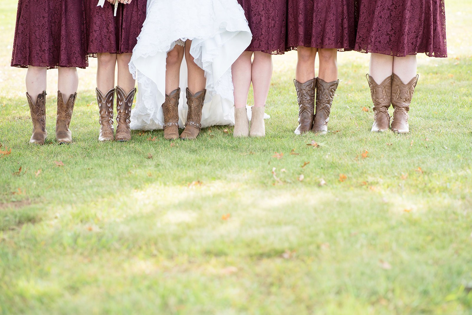 Line of bridesmaids and bride showing matching cowboy boots