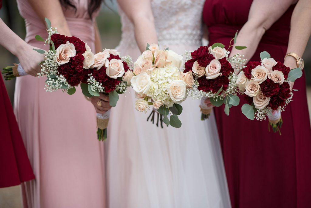 Pink and red mismatched bridesmaids holding out their bouquets