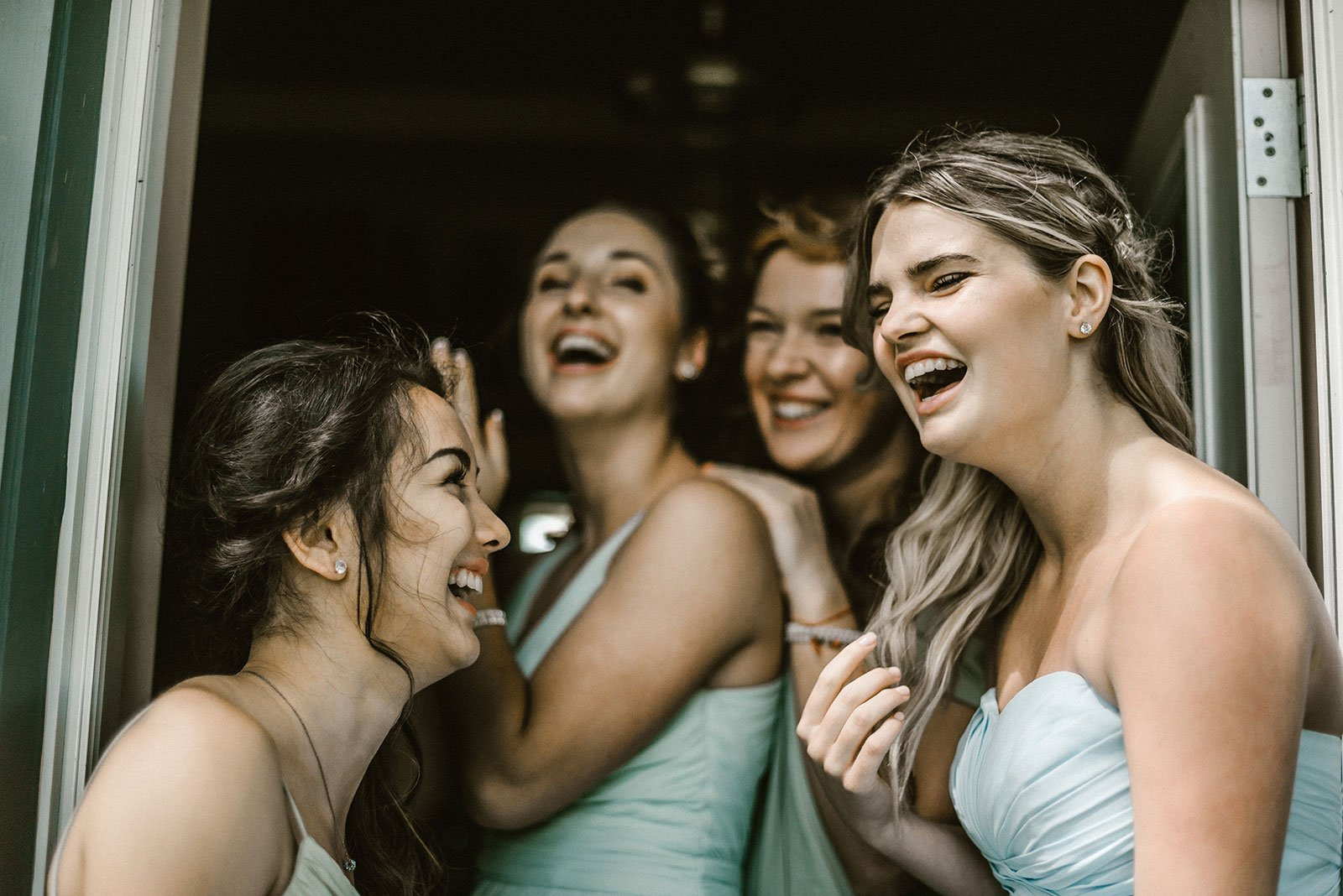Group of bridesmaids standing in a doorway laughing wearing mint green dresses