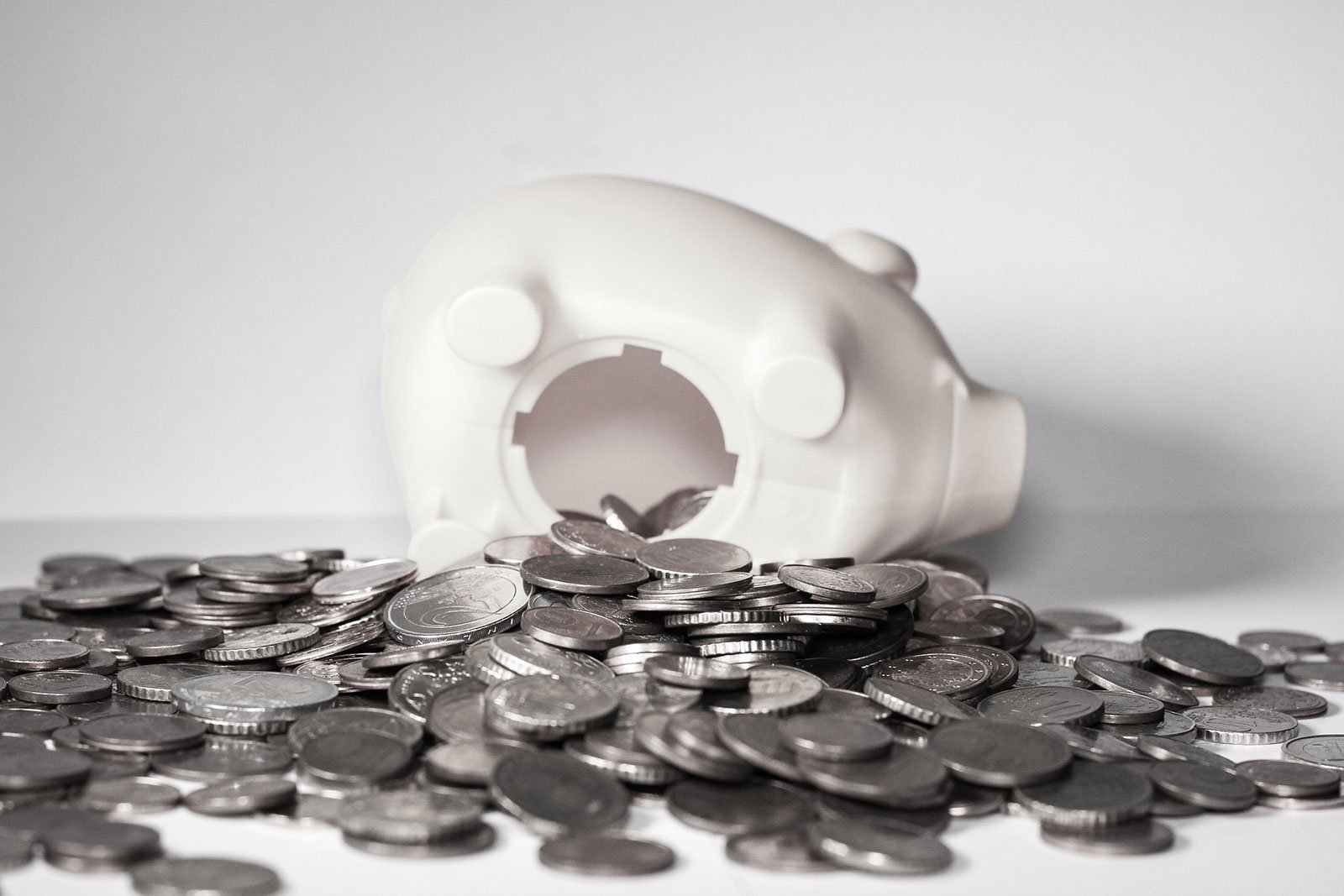 Coins scattered around white piggy bank that has fallen over
