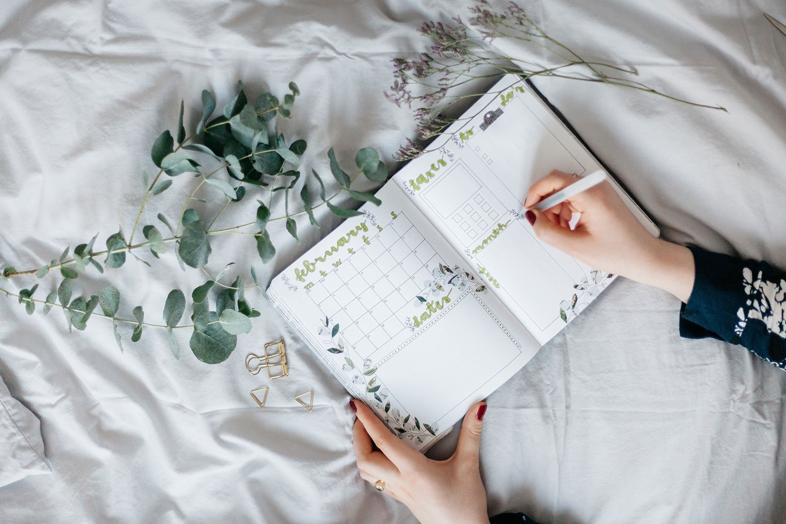 A Girl's hand writing in a green floral wedding planner