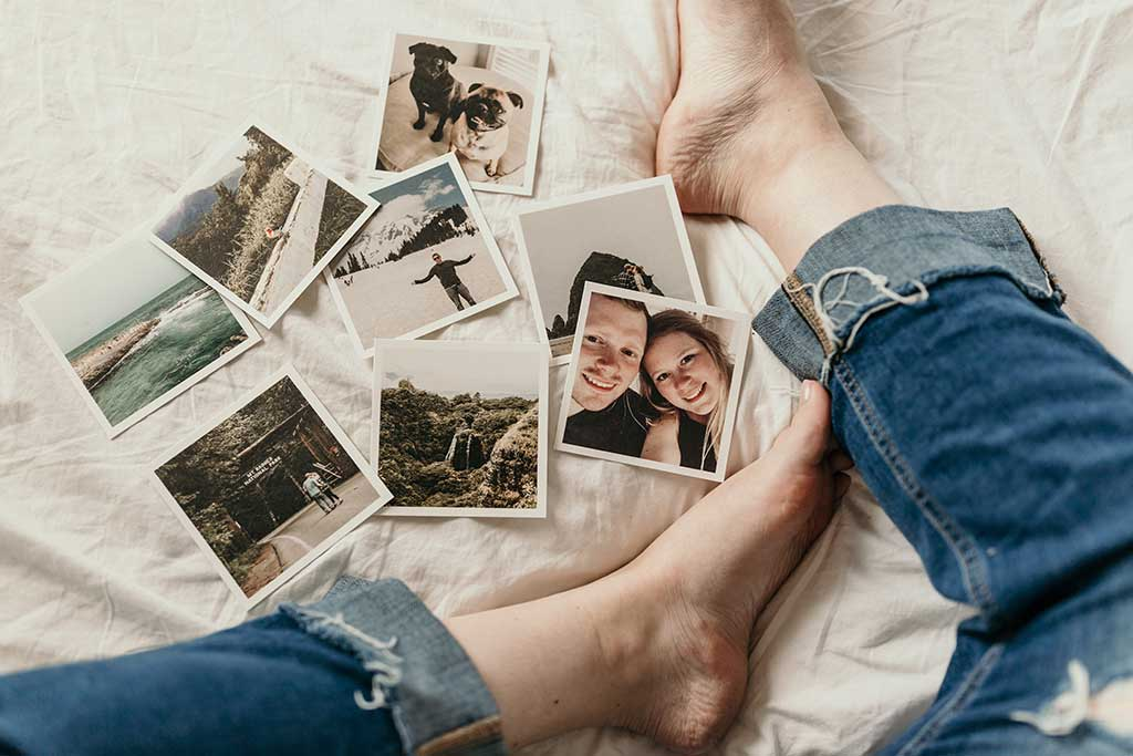 Polaroid pictures on white bed with girl's legs in jeans