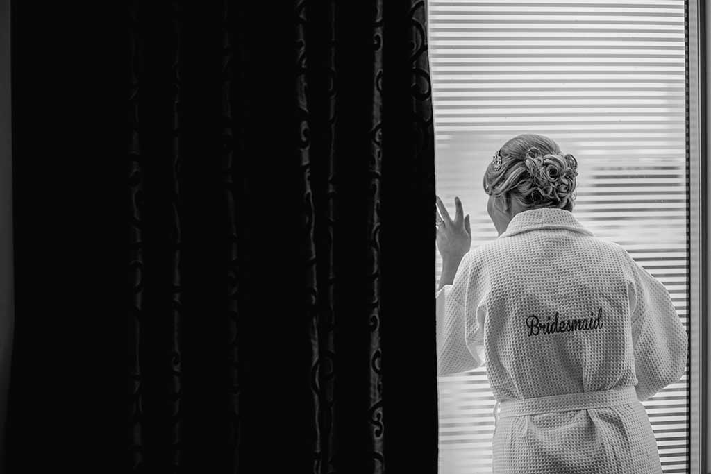 Girl in bridesmaid robe looking out the window in black and white