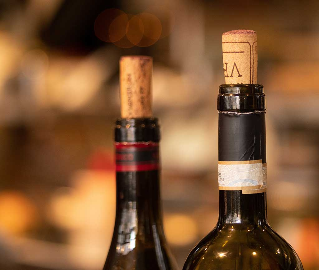 Close up of two corks in wine bottles at a wedding