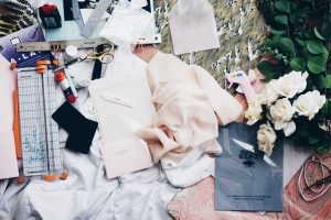 Messy Fashion design workspace with flowers and pink material