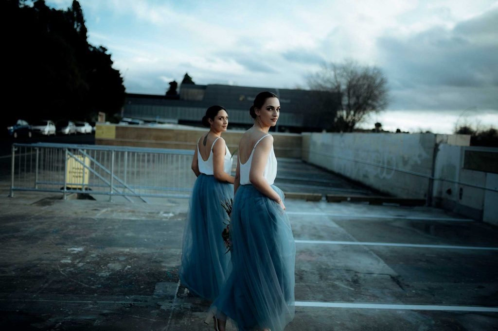 two girls in blue tutu skirt looking back